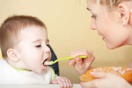 Portrait of young woman feeding her baby son photo