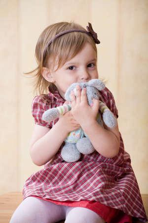 Little joyful girl clasp toy rabbit to one's bosom
