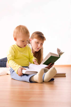 erudition: Cute boy with mother reading a book at home Stock Photo