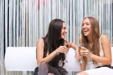 fofoca: Portrait of two happy attractive girl celebrating with champagne