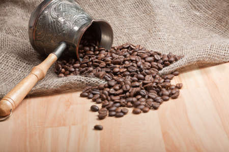 cezve: Sackcloth bag with cezve and roasted coffee beans on table Stock Photo