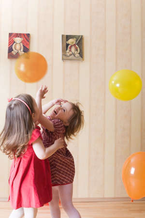Portrait of two little joyful girls playing with airy balls at home photo