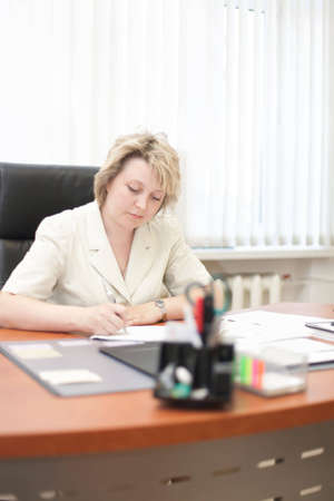 midlife: Mid-life business woman sign document in office Stock Photo