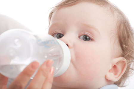 Mother give drink her son by feeding bottle. Over white photo