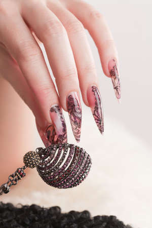 Human hand with long fingernail and beautiful manicure hold beads over gray Banque d'images