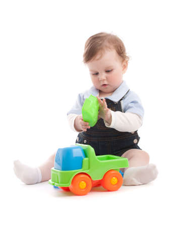 Portrait of adorable baby boy playing with generic toys