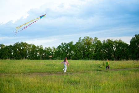 Two kids running on a meadow and fly a kite photo