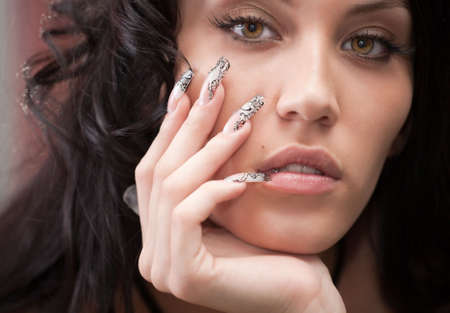 Portrait of attractive girl with beautiful hairstyle and long nails photo