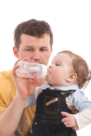 Father give drink her son by feeding bottle. Over white photo
