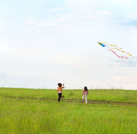 Two little girls running on a meadow and fly a kite photo