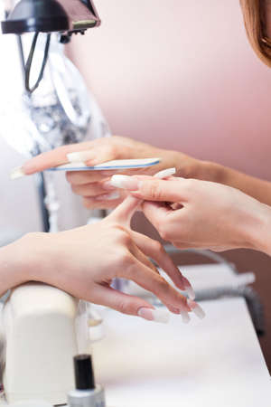 Manicurist treating client at beauty salon. Manicure, painting on nail Stock Photo