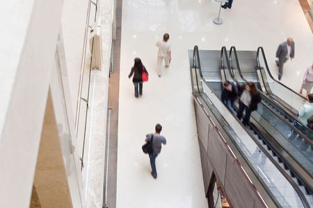 Modern shopping hall with escalator. People in motion blur photo