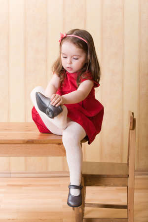 Little girl sitting on table and put on ones shoes