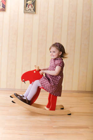 Happy little girl play with toy wooden deer Stock Photo - 5305194