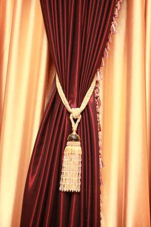 Purple velvet curtain with golden tassel. Close-up