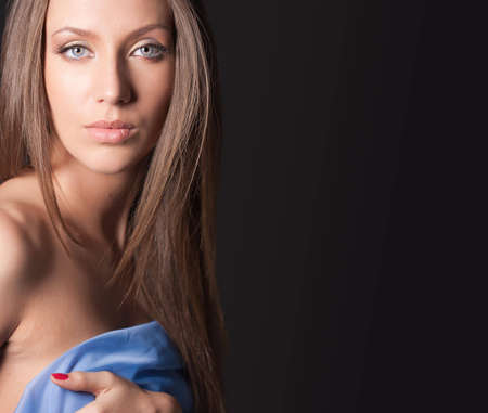 Portrait of attractive girl covering your body in blue silk. Over black with copy space photo