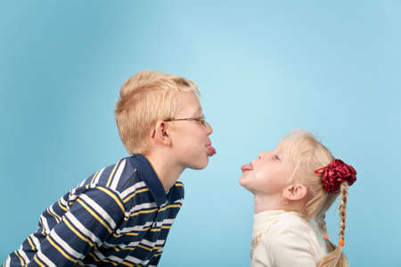 Teenage boy and girl stick out tongues to each other Stock Photo - 5425366
