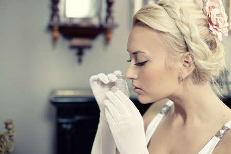 Portrait d'une femme jeune et belle à l'intérieur vintage sentant une bouteille de parfum. Retro style d'image. Banque d'images - 5425352