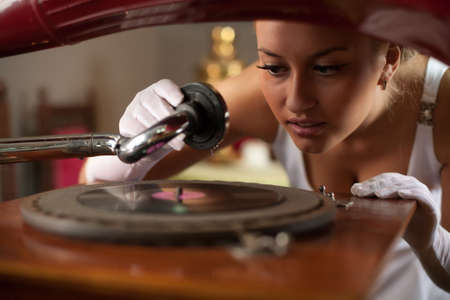 Beautiful young woman in vintage interior start playing music on retro-style gramophone. photo