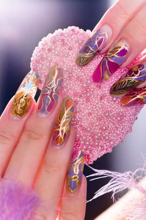 Human fingers with long acrylic fingernail and beautiful manicure holding pink heart photo
