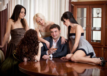 anniversary sexy: Four pretty women seduce � one man in a room Stock Photo