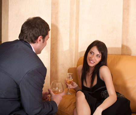 Young happy flirting couple with alcohol drinks in cafe photo