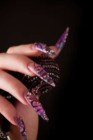 Human fingers with long fingernail and beautiful manicure isolated on black photo