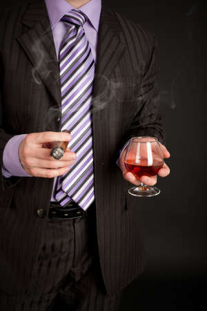 gratification: Successful businessman with glass of cognac and good cigar over black Stock Photo