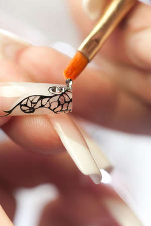 treating: Manicurist treating client at beauty salon. Manicure stage: gluing crystals on nail Stock Photo
