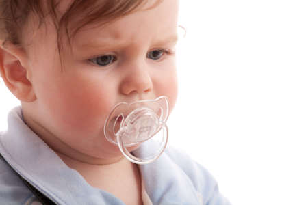 displeased: Portrait of displeased baby boy with pacifier over white Stock Photo