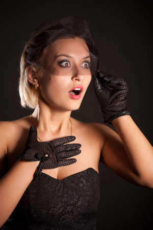 Portrait of amazed retro-style woman in black dress, veil and gloves Фото со стока