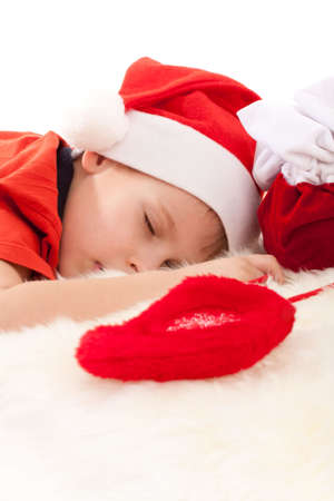 Little boy in Santas hat sleeping and dreaming about gift in christmas sock. Upper part of image isolated on white photo