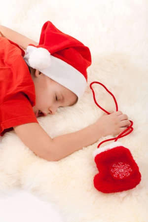 Little boy in Santas hat sleeping and dreaming about gifts in christmas sock. photo