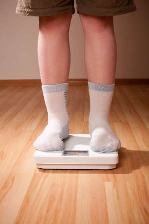sobrepeso: Boy medidas de peso en las escalas de suelo. Las piernas en pantalones cortos y calcetines de pie junto a b�sculas de piso en piso de madera en la sala.