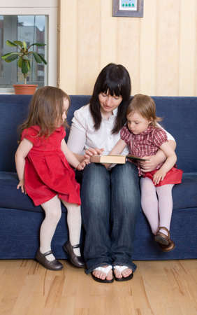 Mother reading a book to her little daughters on sofa at home photo