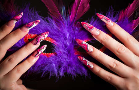 Human fingers with long fingernail and beautiful manicure holding venetian mask photo