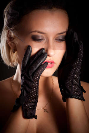 Portrait of attractive retro-style woman in black dress, veil and gloves photo