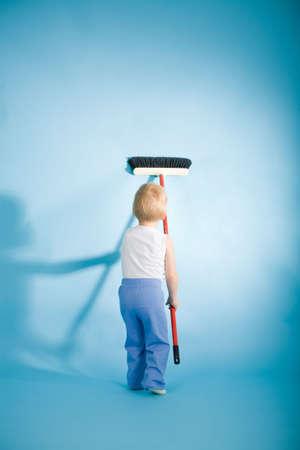 servicio domestico: Chico alegre con hisopo sobre fondo azul de limpieza