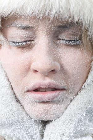 frost: Very cold weather. Close-up portrait of chilled female face covered in ice. Stock Photo