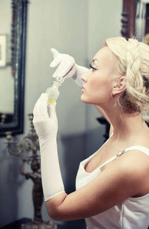Portrait of beautiful young woman in vintage interior smelling a bottle of perfume. Retro style image. photo