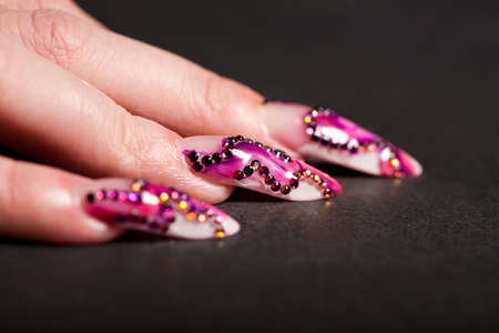 Human fingers with long fingernail and beautiful manicure with crystals over black. Shallow depth of field. Focus on central nail. Фото со стока