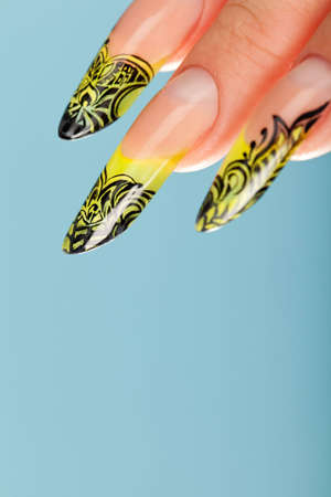Human fingers with beautiful manicure in natural green style over blue photo