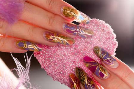 corazon rosa: Dedos humanos con u�a largo acr�lico y hermoso manicura sosteniendo el coraz�n Rosa Foto de archivo
