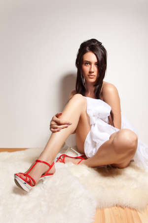 Attractive nude girl sit on the wooden floor and cover your body by white silk cloth photo