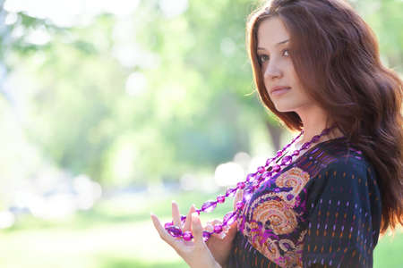 Young happy woman with purple beads at the summer park photo