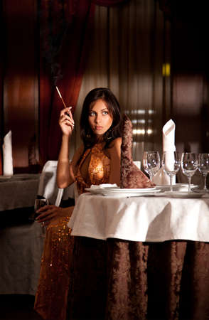 Attractive alone woman smoking cigarette with mouthpiece at restaurant photo