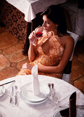 Beautiful girl drinking from a glass of wine at the table in a restaurant photo
