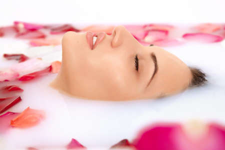 body milk: Attractive girl takes a bath with milk and rose petals. Spa treatments for skin rejuvenation