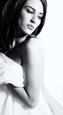 BW portrait of attractive nude girl covering your body by silk cloth. Over white photo