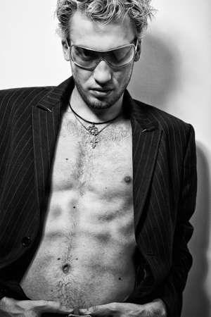 BW portrait of handsome stylish blond man in sunglasses and a coat photo